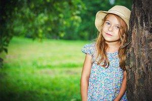 Little girl in the green garden