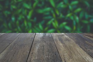 Realistic blank wooden tabletop with green leaves blurred in background - used for product display presentation