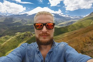 A young traveler wearing spectacles with a beard makes a selfie on the background of Mount Elbrus