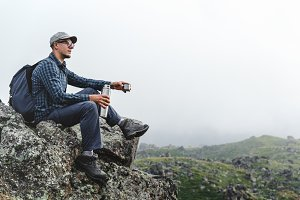 Young male traveler in a shirt, sitting on a rock and drinking coffee or tea from a thermos, while relaxing