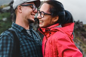 Young couple, man and woman travelers hug, laugh and enjoy a hike