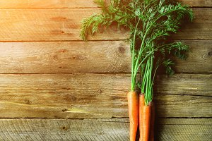 Bunch of fresh organic carrots on a wooden background with sunlights. Concept of diet, raw, vegetarian meal