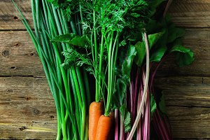 Fresh vegetables - carrots, beetroots, green onion on wooden background. Harvest. Concept of diet, raw, vegetarian meal