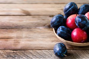Blue and pink organic plums on dark wooden background. Copyspace.