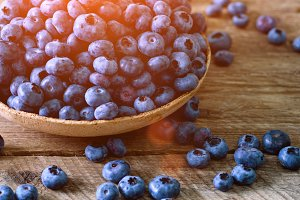 Blueberries on wooden table. Blueberry bowl on vintage background with copyspace. Berries frame, healthy food concept with sunlights
