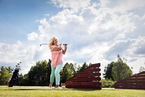 Active senior woman playing golf.