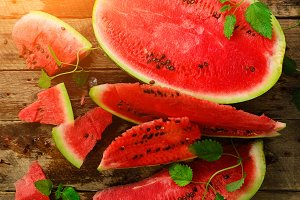 Slices of watermelon with mint leaves on wooden background. Detox and vegetarian concept. Top view, flat lay, copy space