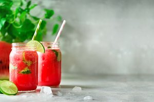 Fresh red watermelon slice and smoothie in glass jar with straw, ice, mint, lime on light background, copy space