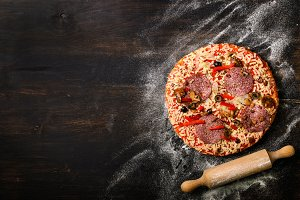 Pizza, rolling pin, flour on dark black background, copy space, top view