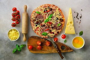 Food ingredients for italian pizza, cherry tomatoes, flour, cheese, basil, rolling pin, board, knife, spices on light grey concrete background. Top view, copy space