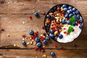 Tasty homemade granola, yogurt, fresh organic berries, pomegranate, mint on rustic wooden background with copy space, top view.