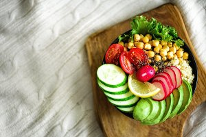 Buddha bowl with avocado, quinoa, cucumber, radish, salad, lemon, cherry tomatoes, chickpea, chia seeds on textile background, copy space