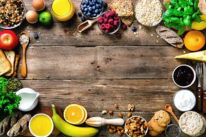 Healthy breakfast ingredients, food frame. Granola, egg, nuts, fruits, berries, toast, milk, yogurt, orange juice, cheese, banana, apple on wooden rustic background, top view, copy space