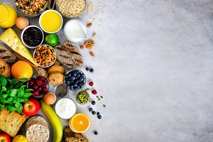 Healthy breakfast ingredients, food frame. Granola, egg, nuts, fruits, berries, toast, milk, yogurt, orange juice, cheese, banana, apple on light grey concrete background, top view, copy space. Banner