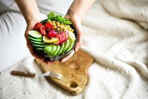 Girl in white jeans holds in hands fork, vegan breakfast meal in bowl with avocado, quinoa, cucumber, radish, salad, lemon, cherry tomatoes, chickpea, chia seeds. Top view, copy space. Clean eating.