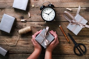 Beautiful woman hands holding gift box on wooden background. Black alarm clock, pen, scissors. Preparing for birthday, christmas, new year. Lifestyle consept