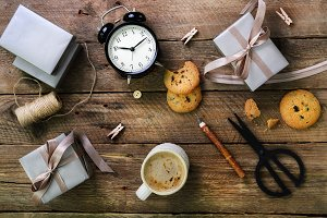 Gift boxes, black alarm clock, pen, scissors on wooden background. Preparing for birthday, christmas, new year.