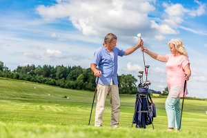 Senior couple choosing equipment for a golf game.
