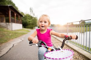 Little girl is cycling in the nature by the lake.