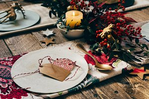 Christmas place setting, name card and rustic Christmas table with ornaments and flower napkin on wooden table