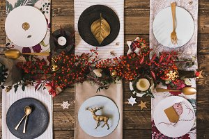 Holiday Gold place setting, funny Christmas table with ornaments and natural berries, on wooden table, overhead shoot