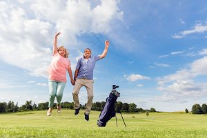 Senior couple jumping on a golf course.