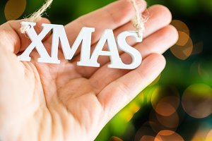 White wooden XMAS letters in hand