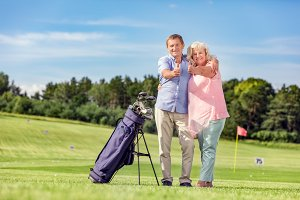 Senior couple giving thumbs up on a golf course.