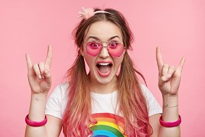 Portrait of excited joyful fashionable female wears pink glasses, bracelets, exclaims with happiness, gestures as shows her positive emotions, being overjoyed. Coquette lovely girl over pink wall
