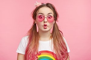 Portrait of fashionable female in pink glasses, has long hair tied in two pony tail, makes grimace, has fun alone as waits for starting party. Woman of fashion. Charming pinup girl models in studio