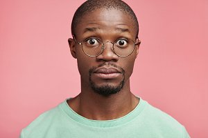 Bug eyed man with dark healthy skin, has full lips, stares through glasses, being terrified to know that he was dissmised for absence from work. Amazed scared Afro American man stand against pink wall