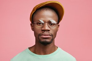 Serious confident dark skinned man wears spectacles and cap, isolated over pink background. Stylish youngster in fashionable clothes looks directly into camera, waits for best friend indoors
