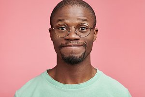 Handsome young African male with beard and mustache, wears round spectacles, presses lips together, has positive expression, looks directly into camera or at interlocutor, discuss something actively