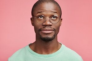 Dark skinned handsome young man looks up, wears spectacles, notices something on ceiling. Clever Afro American male enterpreneur looks at advertisment. People, lifestyle and ethnicity concept