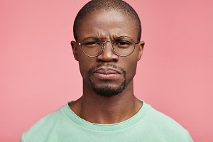 Indoor shot of dark skinned sad discontent African American male, expresses dislike and disappointment, looks strictly at camera, wears casual t shirt and spectacles, isolated over pink background