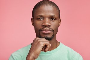 Horizontal portrait of confident serious attractive dark skinned man keeps hand under chin, has full lips, wears casual t shirt, isolated over pink background. Thoughtful male manager poses in studio