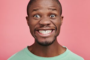Happy glad African American middle aged man pretends to smile, keeps teeth together, looks with bugged eyes, being satisfied with something. Male model poses in pink studio alone, has funny look