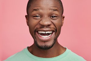Close up portrait of positive black male with dark skin and white perfect teeth, smiles happily as finds out good news, isolated over pink background. Young African man has happy expression.