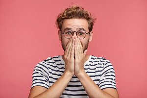 Alarmed nervous hipster guy covers mouth with hands, being shocked or surprised to see unexpected gift prepared by girlfriend. Astonished emotional fearful handsome young male over pink background