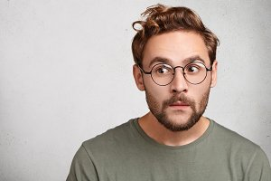 Headshot of attractive stylish youngster or male wonk wears round spectacles, looks curious aside, tries to overhear somethinng important. Caucasian bearded young man with guarded look, worries
