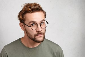 Portrait of young man with specific appearance looks through round glasses, listens attentively to interlocutor, going to speak his mind or prove rightness. People and body language concept.