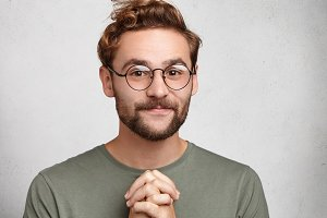 Indoor portrait of delightful bearded young man with trendy hairstyle, keeps palms together, hopes to hear positive results of competition, believes in his victory and good luck. Hope for best