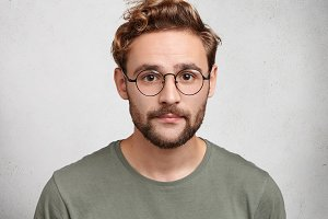 Attractive man with dark eyes, beard and trendy hairdo wears casual clothes and spectacles, looks confidently into camera, poses against white studio wall. Hipster male with clever expression