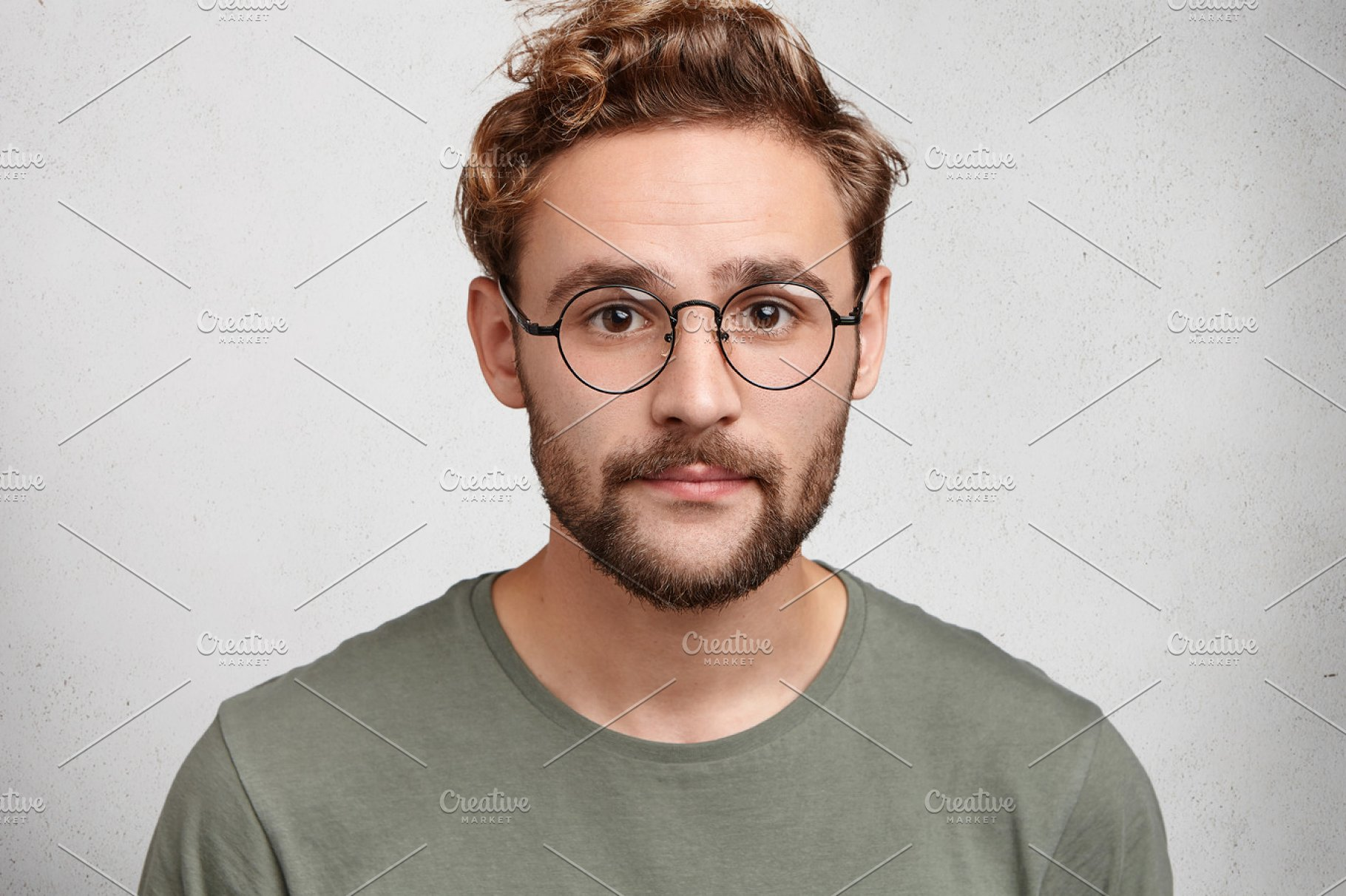 Attractive Man With Dark Eyes Beard And Trendy Hairdo Wears Casual