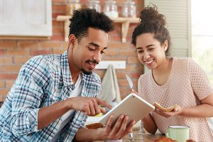 Portrait of mixed race hipster guy shows something at tablet computer to his wife who is busy making sandwhiches, has happy expression, being glad to have pleasant conversation with husband.