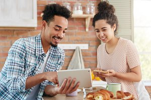 Bearded young man wears checkered shirt shows something on tablet computer to his wife who is making sandwiches, have happy expressions. Family couple does online shopping before having dinner