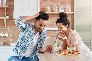 Positive family couple smiles broadly as watches comedy on tablet computer, use free internet connection at home, sit at kitchen table, make breakfast. Woman and man websurf together indoors.