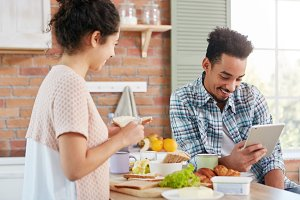 Dark skinned Afro American man dressed casually sits at kitchen with tablet computer, reads news online when his wife makes sandwhiches. Pleased family couple enjoy free time, domestic atmosphere