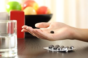 Woman hand holding a vitamin complex