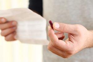 Man hands holding a pill